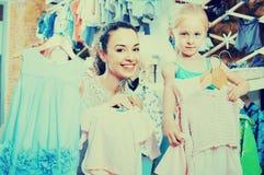 Mère avec du charme avec les enfants de achat de fille vêtements Photos libres de droits