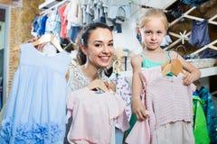 Mère avec du charme avec les enfants de achat de fille vêtements Photographie stock