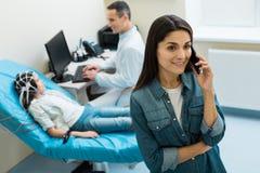 Mère avec du charme de petit patient faisant un appel téléphonique Images libres de droits