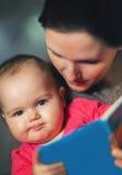 Mère avec du charme montrant des images dans un livre à son petit bébé mignon image libre de droits