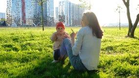 Mère avec l'ébat de bébé sur l'herbe en parc au coucher du soleil La maman embrasse une petite fille dans la nature Photo stock