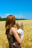 Mère avec l'enfant à la zone de blé Photographie stock libre de droits