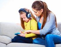 Mère avec l'enfant apprenant à la maison le travail Photo stock