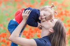 Mère avec l'enfant drôle extérieur au gisement de fleurs de pavot photos stock
