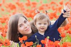 Mère avec l'enfant drôle extérieur au gisement de fleurs de pavot Photographie stock