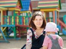 Mère avec l'enfant en bas âge dans le bac à sable Photographie stock libre de droits