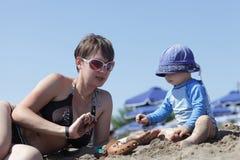 Mère avec l'enfant en bas âge jouant sur une plage Photographie stock libre de droits