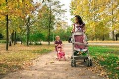 Mère avec l'enfant marchant à travers le stationnement Photos stock