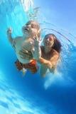 Mère avec l'enfant nageant sous l'eau dans la piscine Images stock