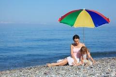 Mère avec l'enfant sous le parapluie sur la plage Photographie stock libre de droits