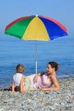 Mère avec l'enfant sous le parapluie sur Pebble Beach Image stock