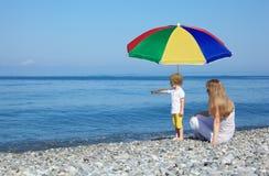 Mère avec l'enfant sous le parapluie sur Pebble Beach Image libre de droits