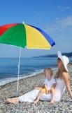 Mère avec l'enfant sous le parapluie sur Pebble Beach Photographie stock libre de droits