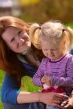 Mère avec l'enfant sur une herbe Photographie stock