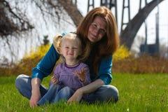 Mère avec l'enfant sur une herbe Photographie stock libre de droits