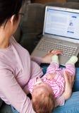 Mère avec l'ordinateur portatif et chéri Images libres de droits