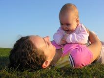 Mère avec la chéri sur le mensonge de coucher du soleil Photographie stock libre de droits