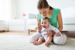 Mère avec la cuillère alimentant le petit bébé à la maison Image libre de droits
