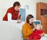 Mère avec la femme mûre donnant le médicament au bébé souffrant Photo libre de droits
