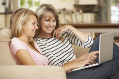 Mère avec la fille adolescente s'asseyant sur Sofa At Home Using Laptop image libre de droits