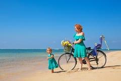 Mère avec la fille avec la bicyclette sur la plage de sable de mer Photo libre de droits