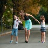 Mère avec la fille d'ADN de fils de naughti sur une promenade en parc Image libre de droits