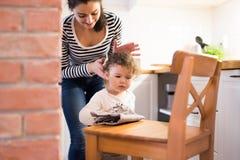 Mère avec la fille dans la cuisine, fille essuyant la chaise Photo libre de droits