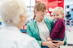 Mère avec la fille dans la pharmacie au compteur photos stock