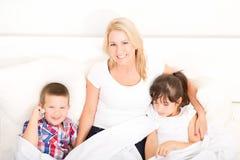 Mère avec la fille et le fils détendant dans le lit Image stock