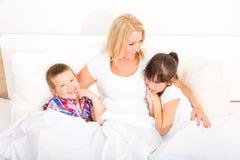 Mère avec la fille et le fils détendant dans le lit Photos libres de droits