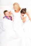 Mère avec la fille et le fils détendant dans le lit Photos stock