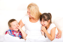 Mère avec la fille et le fils détendant dans le lit Photo stock