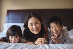 Mère avec la fille et le fils détendant sur le lit dans la chambre de lit Photographie stock libre de droits
