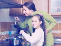 Mère avec la fille faisant cuire à la cuisine images libres de droits