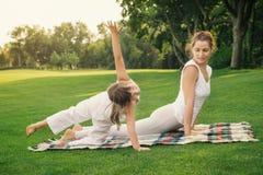 Mère avec la fille faisant l'exercice de yoga images libres de droits