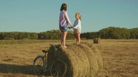 Mère avec la fille jouant sur une meule de foin Famille heureuse ayant l'amusement sur la meule de foin dans le pré Concept de la clips vidéos