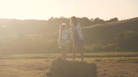 Mère avec la fille jouant sur une meule de foin Famille heureuse ayant l'amusement sur la meule de foin dans le pré Concept de la banque de vidéos