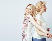 Mère avec la fille posant ensemble le sourire heureux d'isolement sur le fond blanc avec le copyspace, concept de personnes de mo Images libres de droits