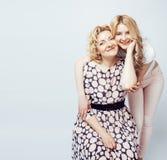 Mère avec la fille posant ensemble le sourire heureux d'isolement sur le fond blanc avec le copyspace, concept de personnes de mo Photo stock