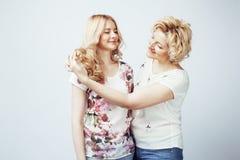 Mère avec la fille posant ensemble le sourire heureux d'isolement sur W Photos libres de droits