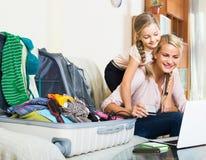 Mère avec la fille près de la valise avec la carte de crédit Photographie stock