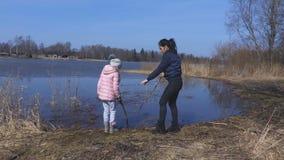 Mère avec la fille près du lac au printemps clips vidéos