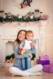 Mère avec la fille souriant et étreignant dans le studio de fête Images stock