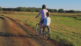 Mère avec la fille sur des bicyclettes dans un pré Famille sur des bicyclettes en nature Le concept de la famille clips vidéos