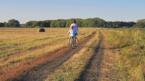Mère avec la fille sur des bicyclettes dans un pré Famille sur des bicyclettes en nature Le concept de la famille banque de vidéos