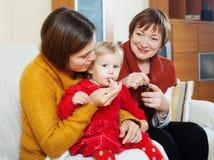 Mère avec la grand-mère donnant le médicament au bébé malade Photos libres de droits