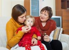 Mère avec la grand-mère mûre s'occupant de l'enfant en bas âge malade Photo libre de droits