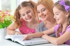 Mère avec la lecture de filles Images libres de droits