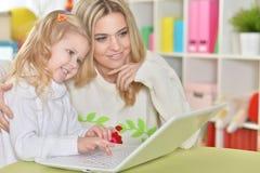 Mère avec la petite fille à l'aide de l'ordinateur portable Photo libre de droits