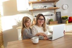 Mère avec la petite fille à l'aide de l'ordinateur portable dans la cuisine image stock